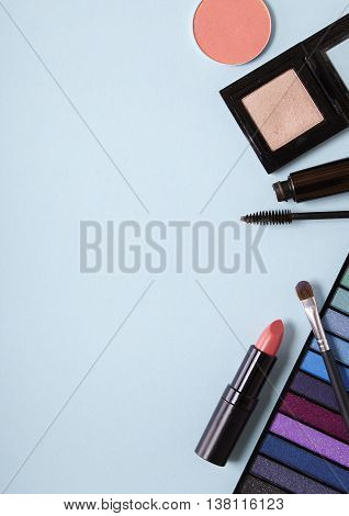 A collection of make up products on a baby blue background forming a page border