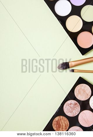 A selection of make up and beauty products arranged on a green background forming a page border