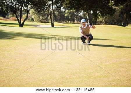 Distant view of golfer crouching and looking his ball on field