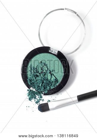 A smashed green eye shadow compact with a make up brush isolated on a white background