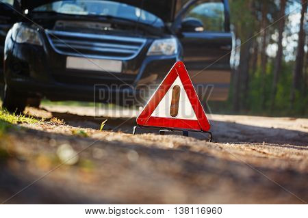 Warning triangle behind a broken down car. Focus on red triangle warning sign.