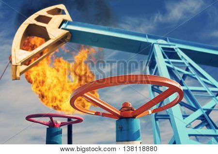 Industrial landscape. Oil valve on background of rocking and torch.