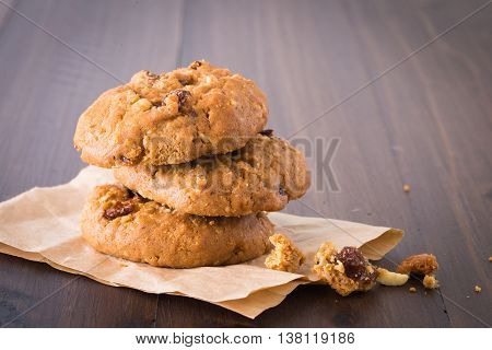 Chocolate Cookies Raisins are stacked three pieces on a wooden floor.