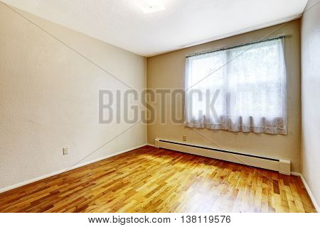 Small Empty Basement Room With Hardwood Floor And Beige Walls