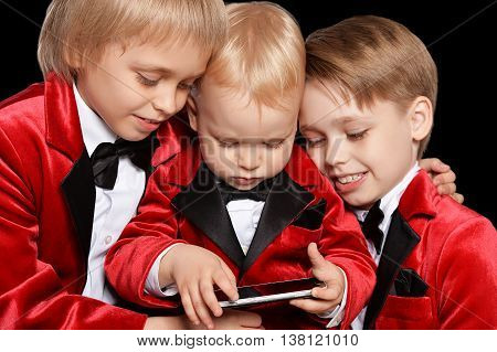 Handsome   little boys in a tuxedo with mobile on black background