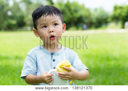 Little boy drink water with plastic botlle