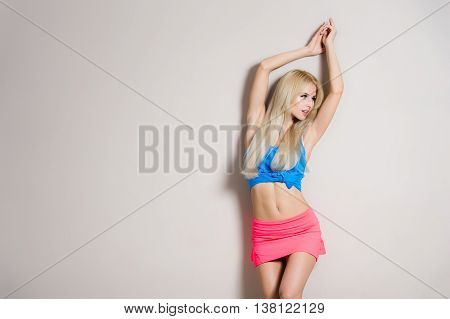 Portrait of pretty sexy fit seductive woman with perfect tan body, long fluffy hairs, in sportive trendy outfit posing on white background. Wearing pink shorts, blue crop top