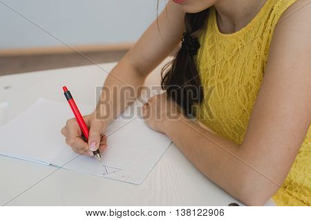 close up of girl's hand with pen doing math, drawing triangle.