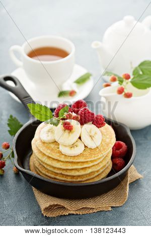 Fluffy buttermilk pancakes with banana and raspberry for breakfast