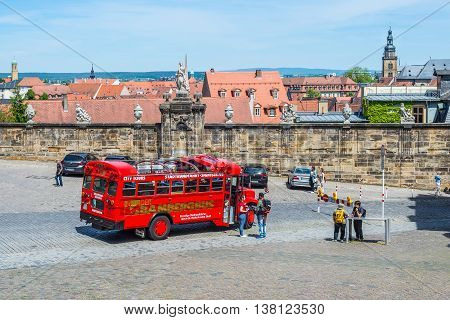 Bamberg Germany - May 22 2016: Local sightseeing bus and tourists near wall with sculptures at the Domplatz of Bamberg Germany. Scenes of tourist activities in a popular travel destination.