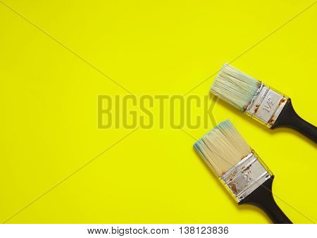 Assorted decorators paint brushes arranged on a yellow background forming a page border