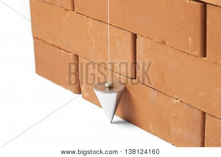 Bricks in masonry with touched plum bob for vertical line isolated on white background