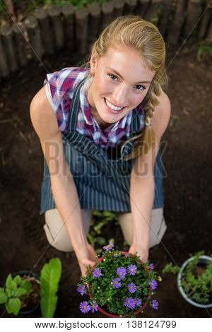 Portrait of beautiful young gardener with potted plant at botanical garden