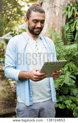Happy young male owner using digital tablet at community garden