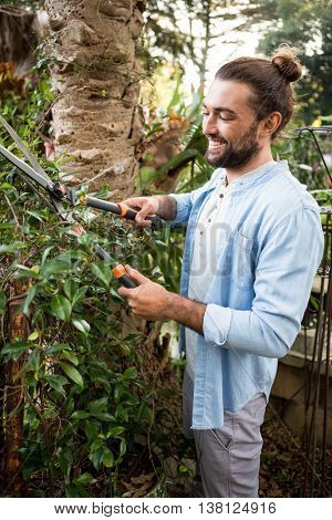 Happy young worker using hedge clippers at community garden