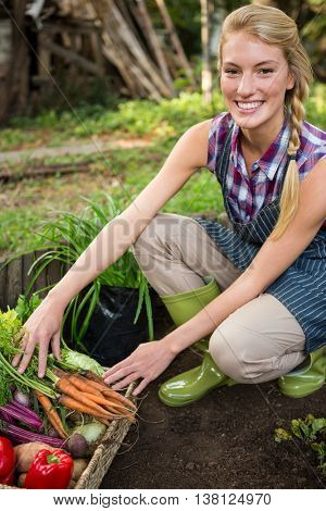 Portrait of beautiful young female gardener with fresh organic vegetables at garden
