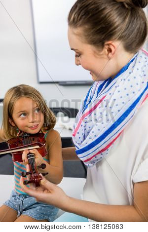 Smiling teacher assisting girl to play violin against in classroom