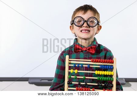 Portrait of cute boy with abacus against whiteboard in classroom