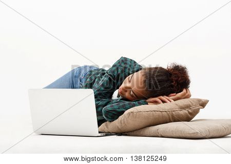 Portrait of young beautiful african girl with laptop sleeping on pillows on floor over white background.