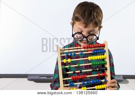 Cute boy playing with abacus against whiteboard in classroom