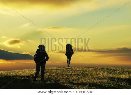 Dos personas subiendo en pastizales en el trekking