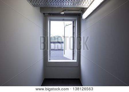 an small emergency exit door at the end of the corridor