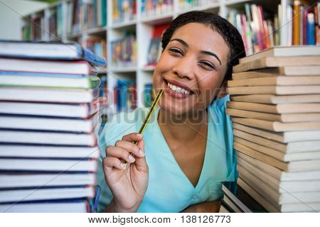 Portrait of thoughtful young woman amidst books in library