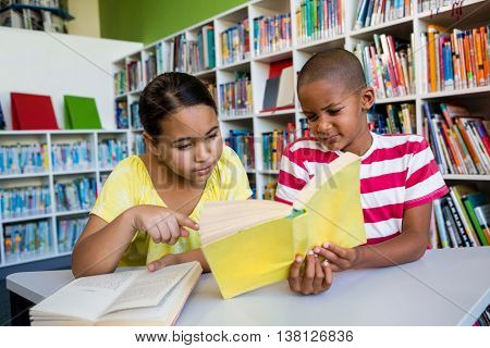 Front view of students reading book against bookshelf at library in school