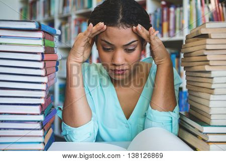 Stressed young woman sitting amidst books in library