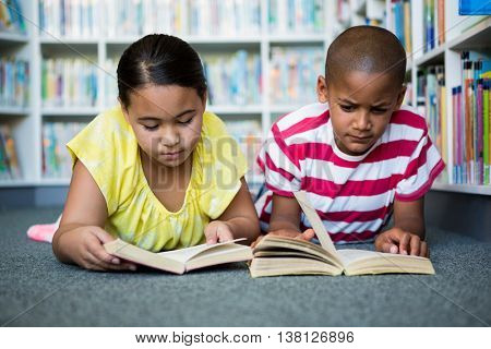 Front view of students reading books while lying at library in school