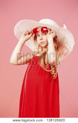 Happy seven year old girl posing in long red dress and white hat. Summer fashion for kids. Studio shot.
