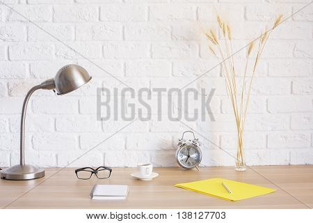 Creative designer desktop with glasses yellow paper sheet alarm coffee cup lamp wheat spikes and other items