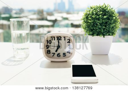 Closeup of white desktop with blank smart phone clock water glass and decorative plant on blurry city background with sunlight. Mock up