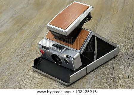 old Instant Camera isolated on wood background