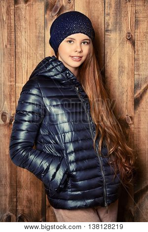 Trendy girl teenager in demi jacket and knitted cap stands by a wooden wall. Modern teen generation. Youth fashion. Healthy hair, haircare.