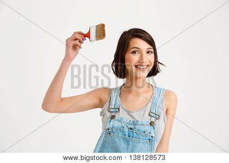 A portrait of young smiling beautiful girl, in gray shirt and denim overall, holding painting brush looking at camera, isolated on white background