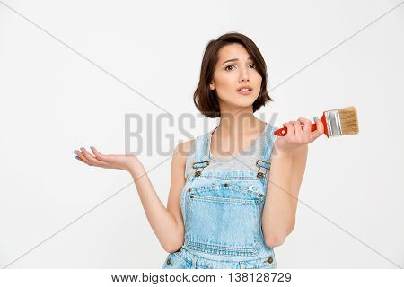 A portrait of young pretty girl, in gray shirt and denim overall, looking amazed, holding painting brush, isolated on white background