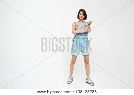 Full length portrait of a seriously pretty girl, in gray shirt and denim overall with crossed hands, holding painting brush, isolated on white background