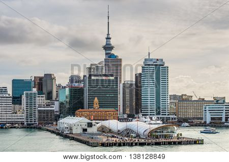 Auckland New Zealand - November 21 2014: New Auckland city central business district & waterfront with the Sky Tower in background with dramatic sky.