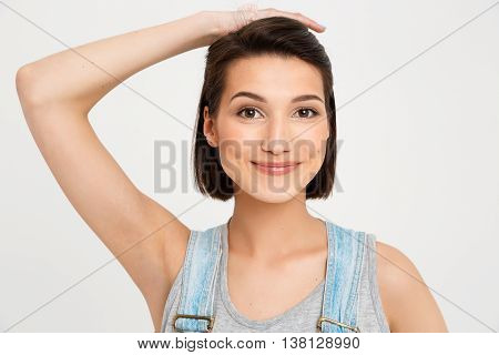 Close-up portrait of young smiling beautiful girl, holding her forelock with hand, looking at camera, isolated on white background