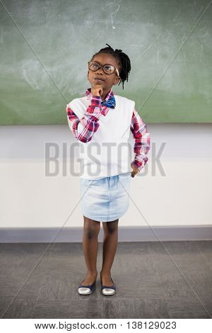 Thoughtful schoolgirl standing with hand on chin in classroom at school