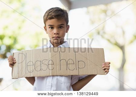 Schoolboy holding placard which reads please help at school