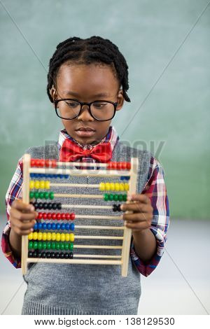 Schoolboy using a maths abacus in classroom at school