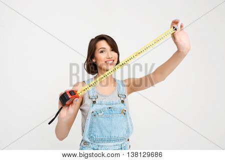 A portrait of young smiling beautiful girl, in gray shirt and denim overall, showing tape measure, looking at camera, isolated on white background
