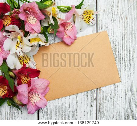 blank paper card with alstroemeria flowers on old wooden table