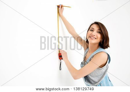 A portrait of young pretty girl, in gray shirt and denim overall, measuring the wall with tape, looking at camera, isolated on white background
