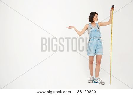 Full length portrait of a seriously pretty girl, in gray shirt and denim overall, holding measure tape, isolated on white background