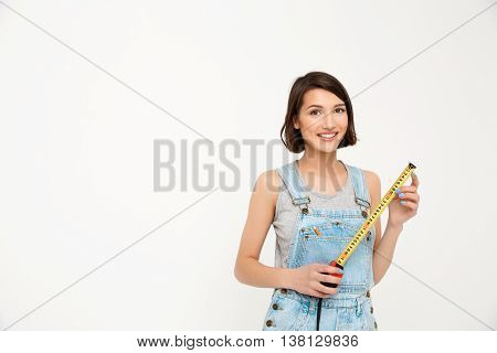 A portrait of young smiling beautiful girl, in gray shirt and denim overall, holding tape measure, looking at camera, isolated on white background
