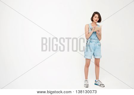 Full length portrait of serious pretty girl, in gray shirt and denim overall, making notes, isolated on white background