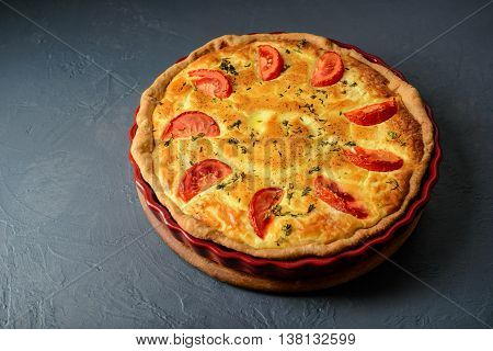 Close-up photo of classic quiche lorraine pie with tomatoes, over grey textural surface